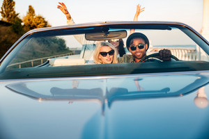 Two happy young couples with raised hands in the car