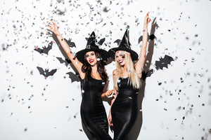 Two happy young women in black witch halloween costumes on party over white background