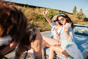 Two happy young women showing peace sign and posing to man photographer outdoors
