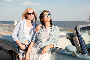 Two happy young women standing and waiting near cabriolet in summer