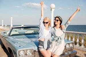 Two happy young women standing with raised hands near vintage cabriolet