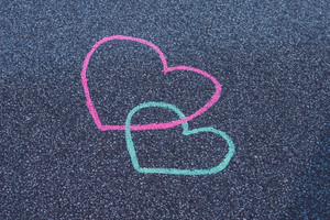Two hearts drawing chalk on the asphalt