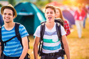 Two hipster teenage boys with backpacks arriving at summer music festival