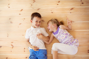 Two kids lying down on the wooden floor in house