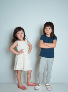 Two little asian sisters in a fashion pose on plain background