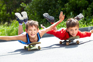 Two little boys lying on their skateboards