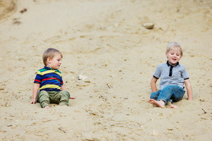 Two little boys on beach at the lake, sitting barefoot in sand. Warm spring day.
