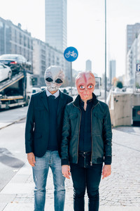 Two man wearing alien masks posing outdoor in the city back light - strange, carnival, halloween concept