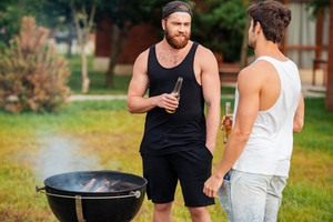 Two men holding a beer bottle while preparing barbecue grill in park zone