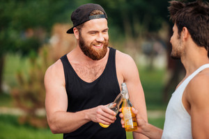 Two men holding a beer bottles outdoors