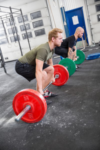 Two men train deadlift at fitness gym center