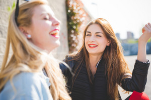 Two millennials young women blonde and brunette friends outdoor in city backlight chatting and laughing - focus on brunette - friendship, happiness, conversation concept