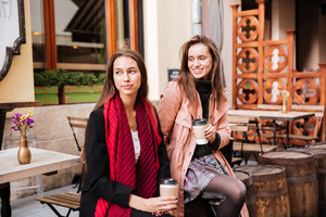 Two models in coats are sitting. with coffee