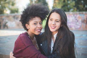 two multiethnic beautiful young woman black and caucasian having fun in town