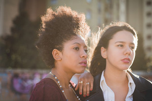 two multiethnic beautiful young woman black and caucasian having fun in town