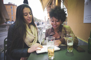 two multiethnic beautiful young woman black and caucasian using tablet in town