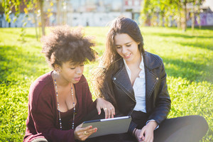 two multiethnic beautiful young woman black and caucasian using tablet sitting in a city park, lookind down the screen smiling - technology, social network, happiness concept