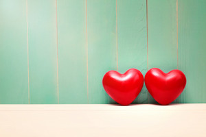 Two red shiny hearts on vintage teal wood