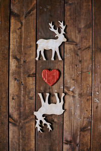 Two reindeers with red heart between them on wooden background