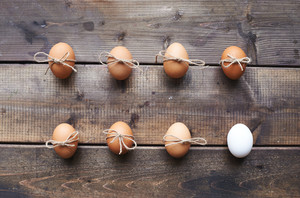Two rows of eggs tied by threads on wooden background
