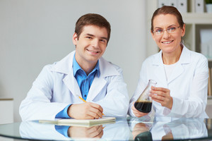 Two scientists looking at camera while working with chemical liquids in laboratory