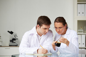 Two scientists looking at glass flask with liquid oil in laboratory while analyzing its characteristics