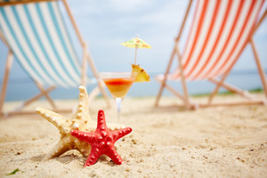 Two sea stars on sandy beach with cocktail on background