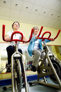 Two senior women practicing on exercise bicycles in gym