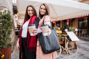 Two smiling attractive young women holding cups of takeaway coffee in old town
