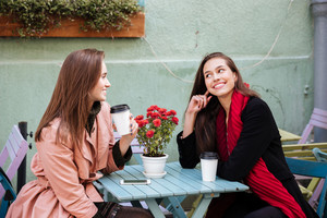 Two smiling beautiful young women drinking coffee and talking in outdoor cafe