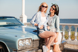 Two smiling beautiful young women standing together near vintage car