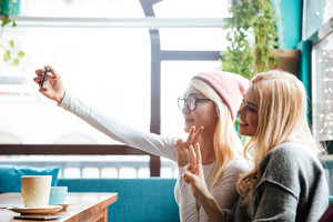 Two smiling beautiful young women taking selfie with mobile phone in cafe