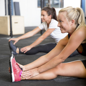 Two smiling women stretching on the floor