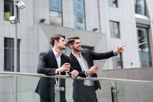 Two smiling young businessmen talking and pointing away outdoors