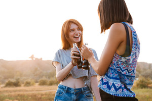 Two smiling young women standing and drinking soda outdoors