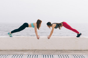 Two sports girls doing sport exercises on the beach in the morning, wide angle shooting