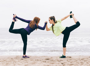 Two sports girls stretching on the beach in the morning