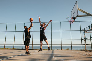 Two sportsmen playing basketball at the playgroud