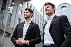 Two successful young businessmen standing near business center