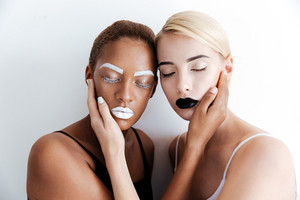 Two tender young women with fashion makeup touching faces of each other over white background