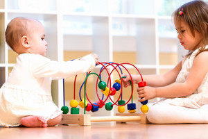 Two toddler girls playing with toys together