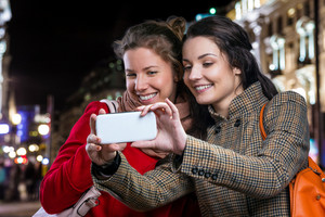 Two women in winter coats taking selfie with smart phone in the night city