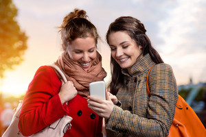 Two women in winter coats with smart phone outside in sunny park