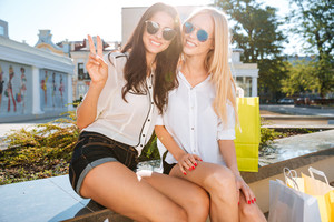 Two women resting on a bench together after shopping and showing victory gesture
