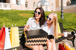Two women resting on a bench together after shopping