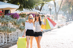 Two women shopping downtown with colorful shopping bags and having fun