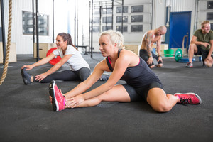 Two women stretching on the floor