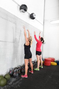 Two women throws medicine balls in fitness gym