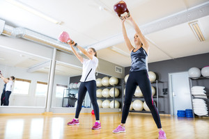 Two women trains with kettlebells at fitness gym