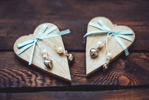 Two wooden hearts with blue ribbons and pearls